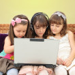 Three little girl in headphones with laptop — Stock Photo