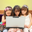 Three little girl in headphones with laptop — Stock Photo #6091340