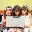 Stock Photo: Three little girl in headphones with laptop