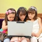 Three little girl in headphones with laptop — Stock Photo