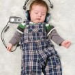 Newborn kid listening music - Stock Photo