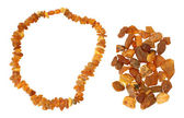 Handful of raw amber and necklace made of it — Stock Photo