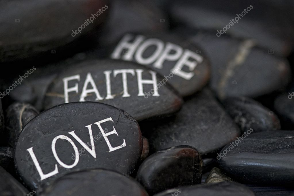 Black pebble with engraved message love, faith, hope  Stock Photo #6733293