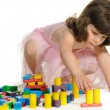 The lovely little girl plays colour wooden cubes — Stock Photo
