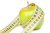 Closeup of a green apple with a measuring tape. Isolated on whit — Stock Photo