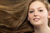 Healthy beautiful long hair closeup in motion created by wind — Stock Photo