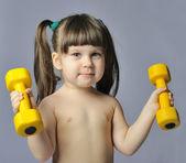 Little girl with dumbbells gray bakcground — Stock Photo