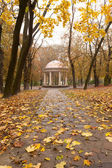 Autumn park with a footpath to summer house — Stockfoto
