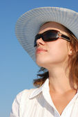 The woman in glasses and a hat on a background of the sky — Stock Photo