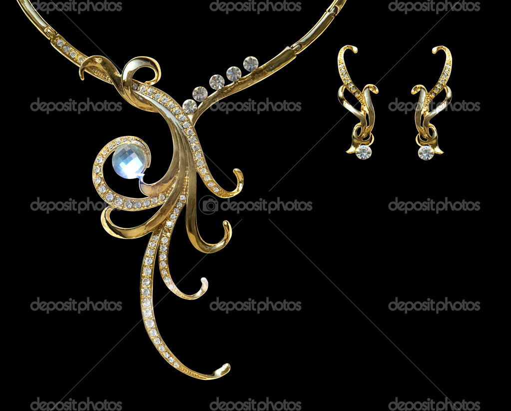 Gold necklace and earring with effect of a luminescence. It is isolated on a black background — Stock Photo #6193422