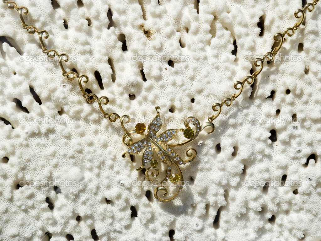 Gold necklace on a background from a sea coral — Stock Photo #6193436