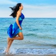 The woman runs on sea coast — Stock Photo