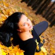 The attractive woman in autumn forest - Stock Photo