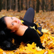 The attractive woman in autumn forest — Stock Photo