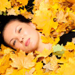 The attractive woman lies in autumn leaf — Stock Photo