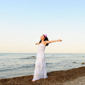The woman in a white sundress on seacoast with open hands — Stock Photo