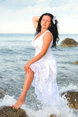 The woman in a white sundress on seacoast. Closed eyes — Stock Photo