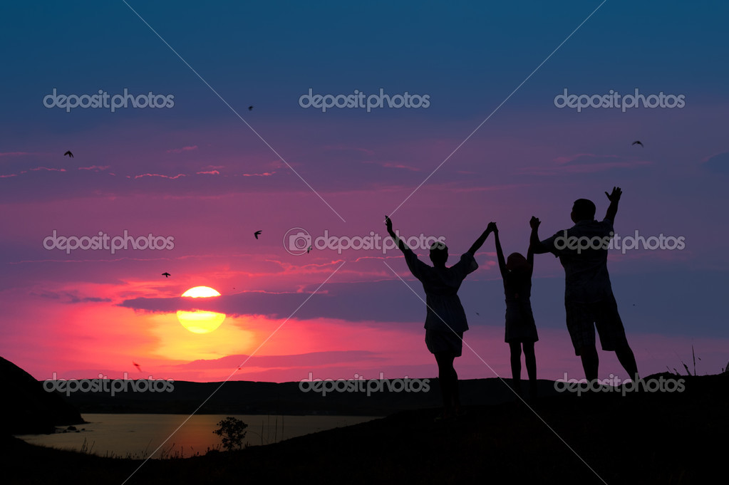 The family from three persons welcomes the sunset sun. — Stock Photo #6632544