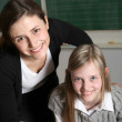 Cheerful teacher and student in the classroom with textbooks. — Stock Photo