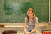 Triest blond meisje in school — Stockfoto