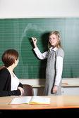 Öğrenci sınıfta tahtaya yazıyor. — Stok fotoğraf