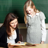 Student and teacher in the classroom look together in a school b — Stock Photo