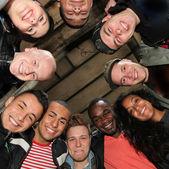 Zehn fröhlich studierende verschiedener nationalitäten in einem kreis — Stockfoto