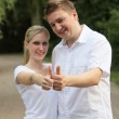 Young couple holding up the thumb — Stock Photo