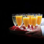 A waiter served orange juice and champagne - square — Stock Photo