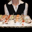 Photo: Waitress serving finger food.