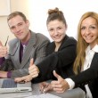 Stock Photo: Positive team in the office shows up the thumb.