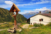 Wooden cross near rural house in Alps. — Stock Photo