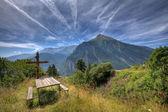 Wooden cross on alpine meadow. — Stock Photo