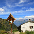Wooden cross near rural house in Alps. — Stock fotografie