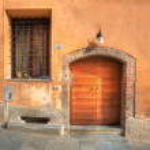 Wooden door and window with bars in Saluzzo. — Stock Photo