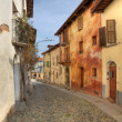 Narrow paved street among houses in Saluzzo, Italy. — Stock Photo