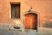 Wooden door and window with bars in Saluzzo. — Stock Photo