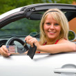Young woman happy about her new drivers license - Stock Photo
