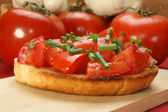 Toasted bread with diced tomatoes and organic chives — Stock Photo