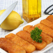 Fried fish sticks on a white plate - Stock Photo