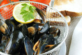Cooked mussels in a colander with lemon — Stock Photo