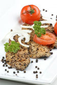 Peppered mackerel with onion rings, tomato and pepper seeds — Stock Photo