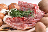 Raw pork with rosemary, potatoes and onions — Stock Photo