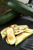 Grilled organic zucchini slices in a pan — Stock Photo