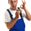 Young craftsmen with blue overall eating a ham sandwich — Stock Photo