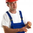 Young craftsmen in work clothes holding a ruler — Stock Photo