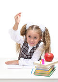 Young girl at a desk, hand raised — Stock Photo