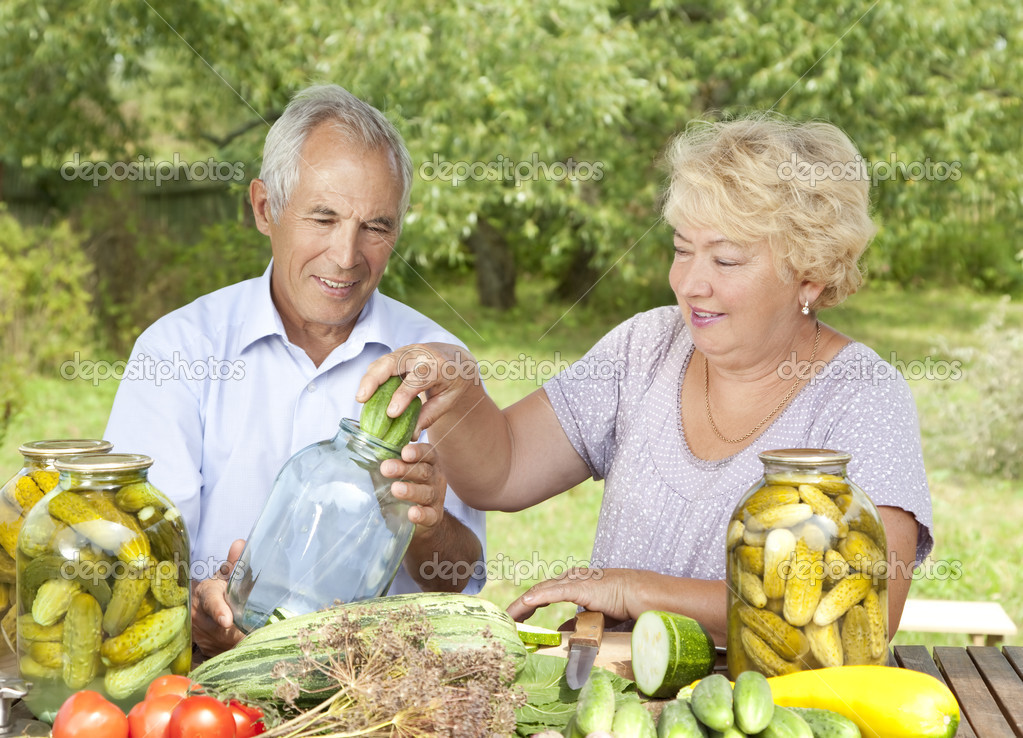 Happy elderly couple making home made pickles — Stock Photo #6642059