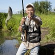 Fisherman fly fishing in a lake - Stock Photo