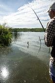 Fisherman fishing on a river bank — Stock Photo
